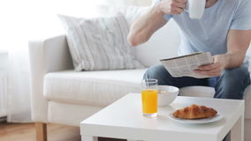 Fermez-vous de l'homme avec le journal prenant le petit déjeuner clips vidéos