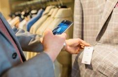 Fermez-vous de l'homme avec le smartphone au magasin d'habillement Images stock