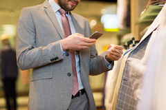 Fermez-vous de l'homme avec le smartphone au magasin d'habillement Photos libres de droits