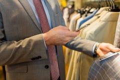 Fermez-vous de l'homme avec le smartphone au magasin d'habillement Images libres de droits