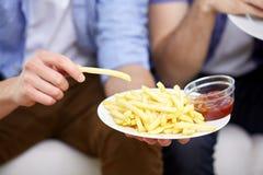Fermez-vous de l'homme avec les pommes frites et le ketchup Photographie stock