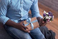 Fermez-vous de l'homme avec plaisir tenant les fleurs et le cadeau Photo stock