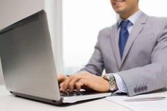 Fermez-vous de l'homme d'affaires avec l'ordinateur portable et les papiers photographie stock