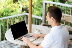 Fermez-vous de l'homme d'affaires avec l'ordinateur portable sur la terrasse photos stock