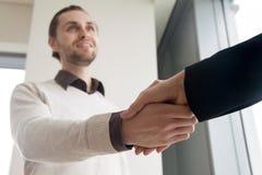 Fermez-vous de l'homme d'affaires de poignée de main, de sourire et du client secouant l'ha image stock
