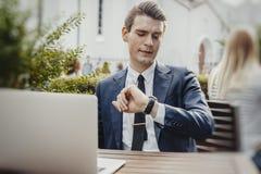 Fermez-vous de l'homme d'affaires jugeant le téléphone portable disponible et regardant des montres photographie stock libre de droits