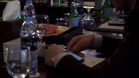 Fermez-vous de l'homme d'affaires s'asseyant ? la barre et lisant quelque chose sur son smartphone barre Vue de c?t? de jeune hom photo stock