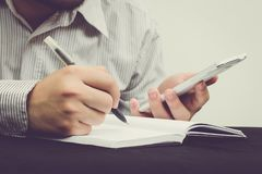 Fermez-vous de l'homme d'affaires tenant un stylo et écrivant la note de recherches photographie stock