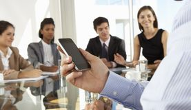 Fermez-vous de l'homme d'affaires Using Mobile Phone au cours de la réunion du conseil d'administration autour du Tableau en verr Photo stock