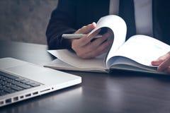 Fermez-vous de l'homme d'affaires vérifiant des documents sur le bureau photographie stock libre de droits