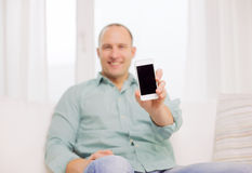 Fermez-vous de l'homme de sourire avec le smartphone à la maison Photos libres de droits