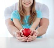 Fermez-vous de l'homme et de la fille tenant la forme rouge de coeur Photos stock