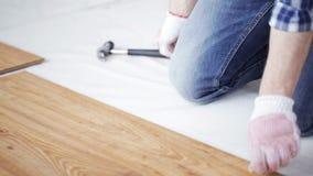 Fermez-vous de l'homme installant le plancher en bois clips vidéos