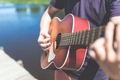 Fermez-vous de l'homme jouant la guitare acoustique contre le beau lac ou rivière image stock