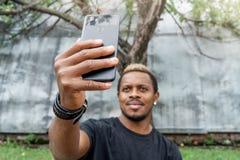 Fermez-vous de l'homme ? la peau fonc?e dans le T-shirt noir faisant le selfie au t?l?phone portable photo libre de droits