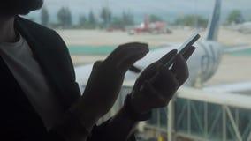 Fermez-vous de l'homme mettant en rouleau l'écran de son smartphone dans l'aéroport clips vidéos