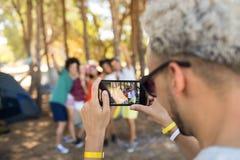 Fermez-vous de l'homme photographiant des amis avec le smartphone Photo stock