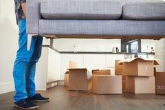Fermez-vous de l'homme portant la nouvelle maison de Sofa As He Moves Into Photographie stock libre de droits