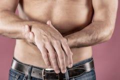 Fermez-vous de l'homme souffrant de la douleur dans son poignet sur le fond rose concept de soins de santé et de problème photos stock