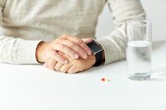 Fermez-vous de l'homme supérieur avec l'eau, la pilule et la montre Photo libre de droits