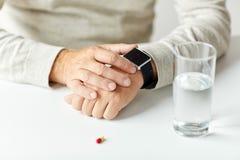 Fermez-vous de l'homme supérieur avec l'eau, la pilule et la montre Images libres de droits
