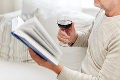 Fermez-vous de l'homme supérieur avec le livre de lecture de vin Photo stock