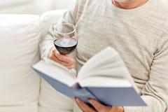 Fermez-vous de l'homme supérieur avec le livre de lecture de vin Photographie stock
