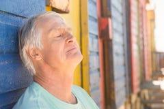 Fermez-vous de l'homme supérieur détendant par la hutte de plage Photo stock