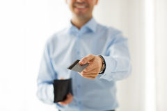 Fermez-vous de l'homme tenant le portefeuille et la carte de crédit Photos stock