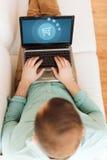 Fermez-vous de l'homme travaillant avec l'ordinateur portable à la maison Photos stock