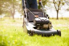 Fermez-vous de l'homme travaillant dans l'herbe de coupe de jardin avec la faucheuse Photographie stock libre de droits