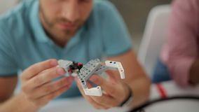 Fermez-vous de l'ingénieur masculin examinant le détail robotique de bras banque de vidéos