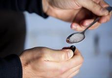 Fermez-vous de l'intoxiqué préparant la drogue de crack photographie stock