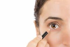 Fermez-vous de l'oeil d'une femme appliquant l'eye-liner Photographie stock
