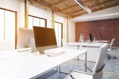 Fermez-vous de l'ordinateur dans un bureau de mur de briques, modifié la tonalité Photo libre de droits