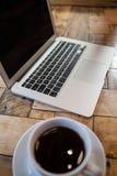 Fermez-vous de l'ordinateur portable et du café Photo stock