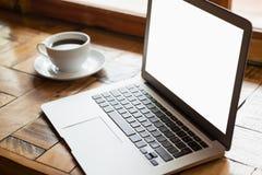 Fermez-vous de l'ordinateur portable numérique par la tasse de café sur la table en bois Photo libre de droits