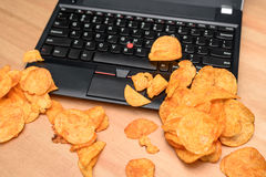 Fermez-vous de l'ordinateur portable ouvert avec des puces dispersées sur le clavier Image libre de droits