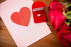 Fermez-vous de la bague à diamant, des roses et de la carte de voeux Photographie stock libre de droits