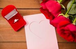 Fermez-vous de la bague à diamant, des roses et de la carte de voeux Photos stock