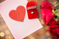 Fermez-vous de la bague à diamant, des roses et de la carte de voeux Images stock