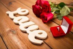 Fermez-vous de la bague à diamant, des roses rouges et de l'amour de mot Photos stock