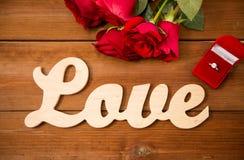 Fermez-vous de la bague à diamant, des roses rouges et de l'amour de mot Images libres de droits