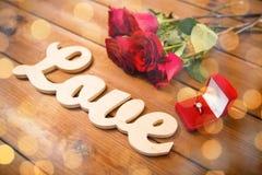 Fermez-vous de la bague à diamant, des roses rouges et de l'amour de mot Photo libre de droits