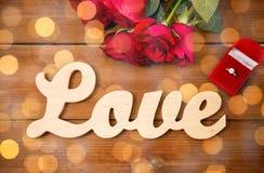 Fermez-vous de la bague à diamant, des roses rouges et de l'amour de mot Photo stock