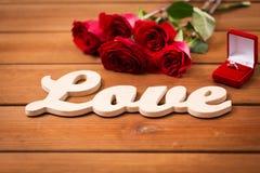 Fermez-vous de la bague à diamant, des roses rouges et de l'amour de mot Photos libres de droits