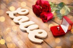 Fermez-vous de la bague à diamant, des roses rouges et de l'amour de mot Images stock
