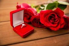 Fermez-vous de la bague de fiançailles de diamant et des roses rouges Images stock