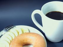 Fermez-vous de la banane et du beignet avec du café noir dans la tasse blanche franc Image libre de droits