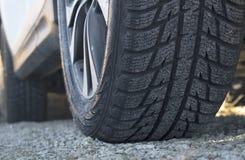 Fermez-vous de la bande de roulement de pneu d'hiver du ` s de voiture sur la route de gravier Images stock